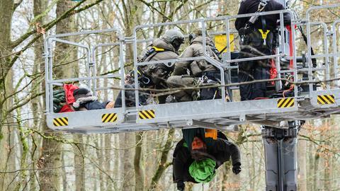Ein Waldbesetzer hängt kopfüber von einem Hubwagen der Polizei