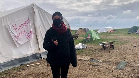 Junge Frau mit Maske vor Zelten