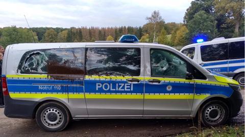 Ein Polizeiauto mit eingeschlagenen Scheiben und Farbresten