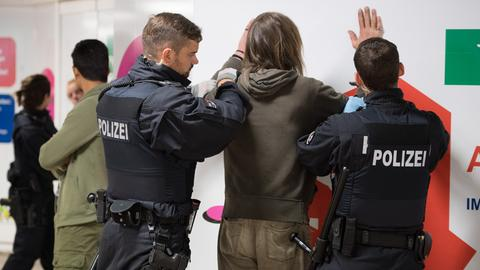 Polizisten durchsuchen am Frankfurter Hauptbahnhof einen Verdächtigen nach Drogen.