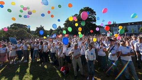 Demo-Teilnehmer lassen in Kassel Luftballons steigen.