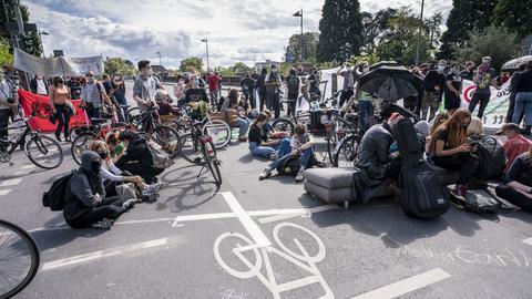 """Demonstranten der Bewegung """"Fridays for Future"""" blockieren bei einem Protestzug eine Kreuzung vor dem Mainkai in Frankfurt"""