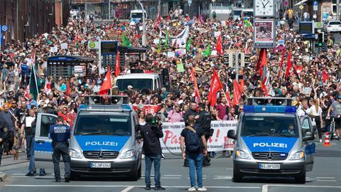 Gegendemonstranten in Kassel - davor zwei Polizeifahrzeuge