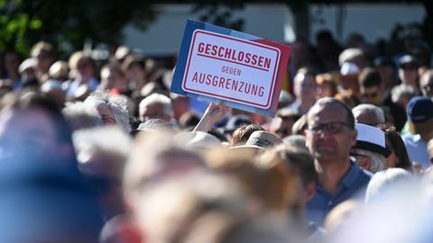 """Menschenmenge demonstriet, einer hält Schild """"Geschlossen gegen Ausgrenzung"""""""