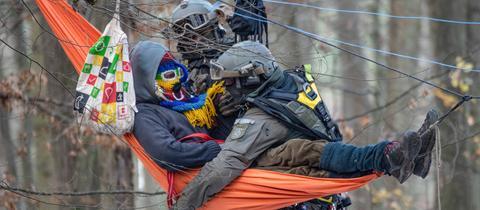 Ein Waldbesetzer in einer Hängematte wird von Einsatzkräften der Polizei geborgen.