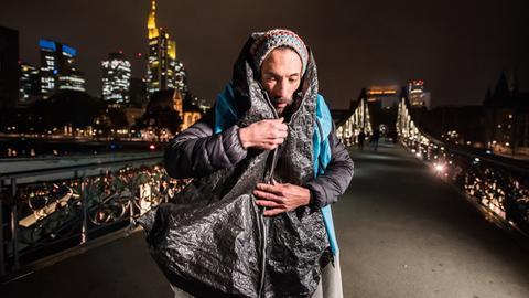 Designer Radames Eger mit einem seiner Spezialmäntel für Obdachlose auf dem Eisernen Steg in Frankfurt.