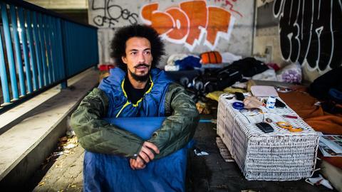 Modedesigner Radames Eger mit seinem Multifunktionsmantel in einem Obdachlosenlager
