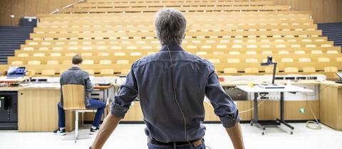 Ein Professor hält eine Online-Lehrveranstaltung in einem menschenleeren Hörsaal.