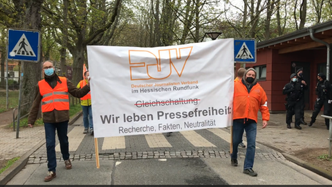 Mitglieder des Journalisten-Verbandes ziehen durch die Straßen vor dem Hessischen Rundfunk.