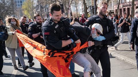 Polizisten führen einen Demonstranten ab