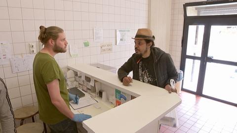 Einblicke in den Druckraum. Ein Mitarbeitern am Empfang redet mit einem Nutzer des Angebotes.