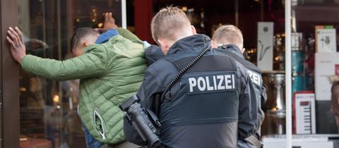 Polizisten kontrollieren im Frankfurter Bahnhofsviertel einen mutmaßlichen Dealer.