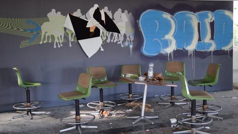 Tische und Müll stehen vor einer beschmierten Wand