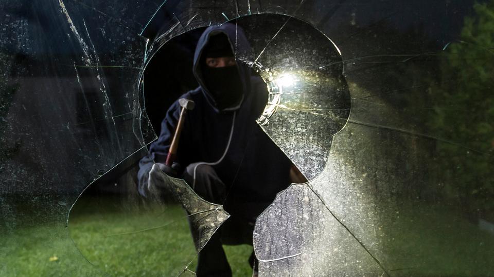 Durch eine eingeschlagene Fensterscheibe blickt ein Einbrecher (gestellte Szene).