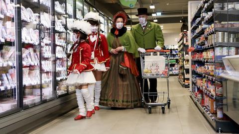 Verkleidete Karnevalisten gehen im Supermarkt einkaufen.