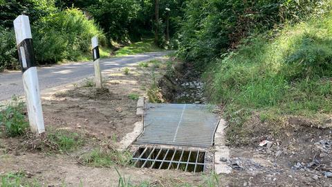 Wassereinlauf mit einem Gitter - neben einer Straße bei Willingshausen.