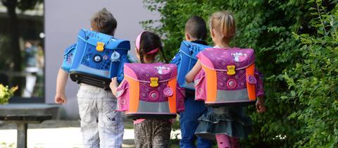 Vier Schulkinder laufen auf Bürgersteig