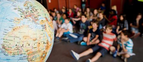 Kinder sitzen auf dem Boden vor Globus