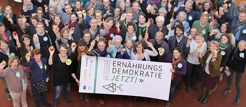 Knapp 100 Menschen winken in die Kamera, halten Gemüse und Plakat hoch mit dem Titel Ernährungsdemokratie jetzt