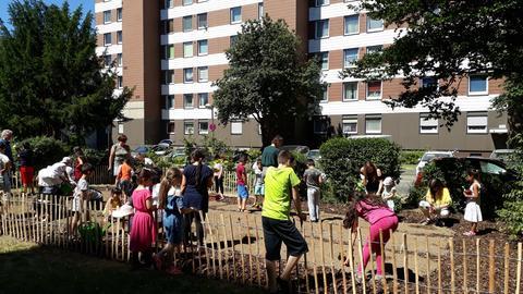 Menschen bearbeitet einen Garten vor einer Häuserfassade