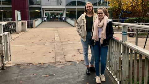 Zwei junge Frauen die in die Kamera blicken, draußen vor dem Hörsaalgebäude der Uni Marburg