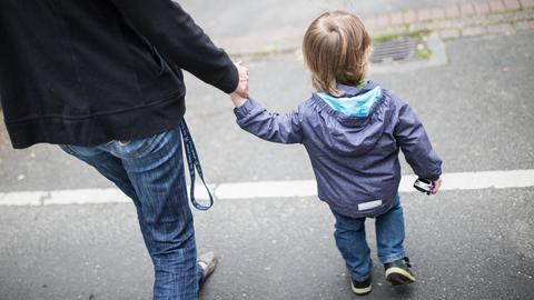 Kind an Hand von Elternteil