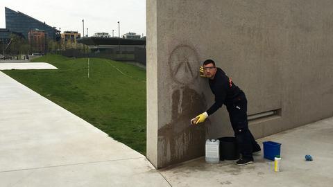 Anti-rassistisches Saubermachen: Ein Mann entfernt die Schmiererei an der Deportations-Gedenkstätte.