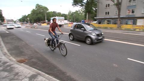 Fabian Berger fährt mit seinem Fahrrad auf einer vielbefahrenen Straße in Kassel