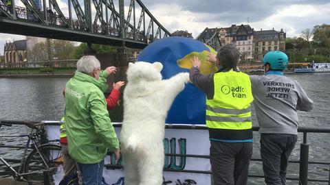 Ein Mann im Eisbärkostüm und weitere Demonstrierende versenken symbolisch eine Erdkugel im Main.