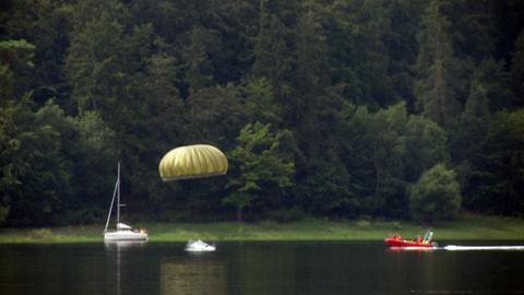 Ein Fallschirmspringer landet im Edersee.