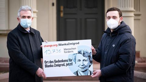 Frankfurts OB Feldmann und Ruben Gerczikow halten ein Schild mit der Forderung nach einem Denkmal für die von einem Rechtsterroristen ermordete Blanka Zmigrod