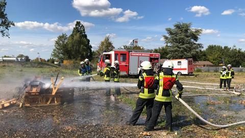 Schüler in Feuerwehrmontur beim Löschen eines kleinen Feuers