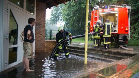 Feuerwehr pumpt nach Unwetter Gebäudeeingang aus