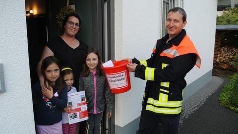 Feuerwehrmann übergibt Löschkübel