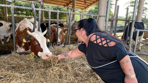 Bewohnerin vom Hof Fleckenbühl füttert eine Kuh mit Stroh