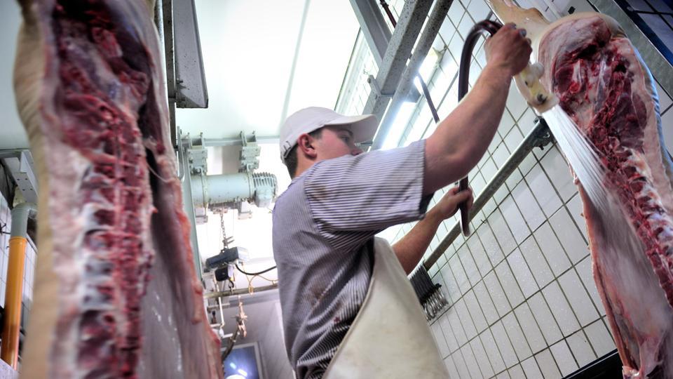 Ein Schlachter zerteilt Schweine in einer Hausschlachterei.