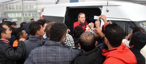 Flüchtlinge in der Erstaufnahmeeinrichtung in Calden stehen vor einem Fahrzeug an