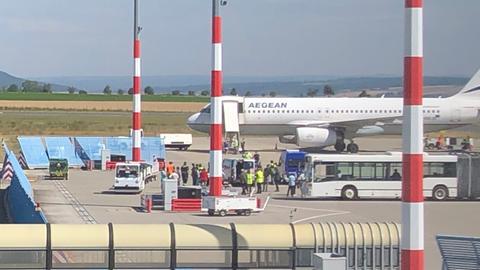 Flugzeug der Aegean Airlines, davor Menschen und Busse.
