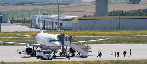 Menschen steigen aus einem Flugzeug der Aegean Airlines aus.