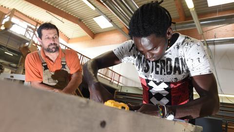 Ein Asylbewerber und künftiger Auszubildender arbeitet in einer Schreinerei an einer Tür
