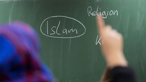 """Eine Schülerin mit Kopftuch meldet sich im Unterricht. An der Tafel prangt das Wort """"Islam"""""""