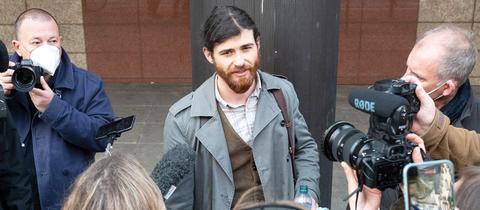 Das Foto zeigt den Angeklagten Franco A. umzingelt von Pressemenschen, wie er mit ihnen redet.