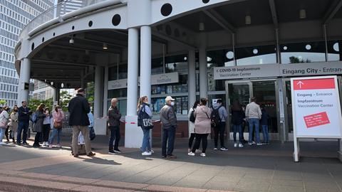 Menschen stehen Schlange vor einer Tür zur Frankfurter Messe