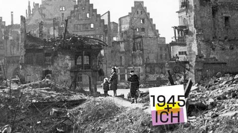 Drei Menschen stehen in einer Schuttlandschaft mitte in Frankfurt 1945.