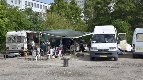 Auf dem geschotterten Platz stehen mehrere umgebaute Busse und Wohnmobile. In der Mitte ist eine Plane gespannt, unter der die Gruppe sitzt.
