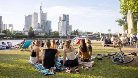 Menschen sitzen am Frankfurter Mainufer mit Blick auf die Skyline.