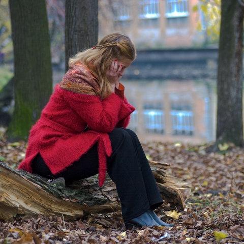 Frau, die in einem Stadtwald zusammengekauert auf den Boden sitzt und vor sich hin starrt.