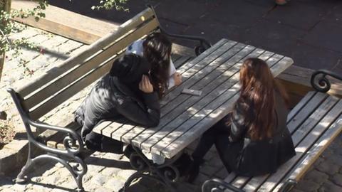 Drei Frauen sitzen an einem Tisch, die Gesichter von ihren Haaren verdeckt.