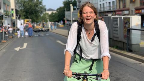Eine junge Frau mit blonden, lockigen Haaren steht mit ihrem Fahrrad auf der Straße und lacht.