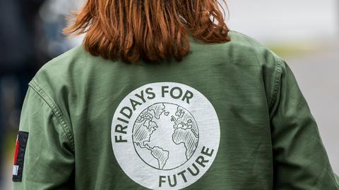 Eine Demonstrantin trägt eine Jacke mit dem Fridays-for-Future-Logo auf dem Rücken.